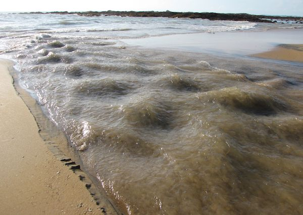photo of rushing water joining the sea