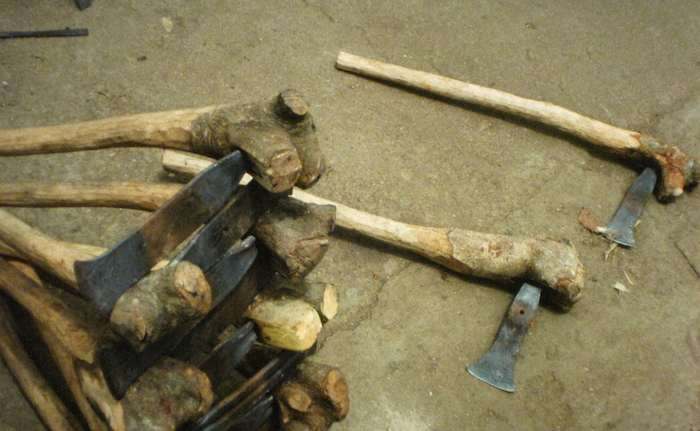 photo of axes with rough wooden handles