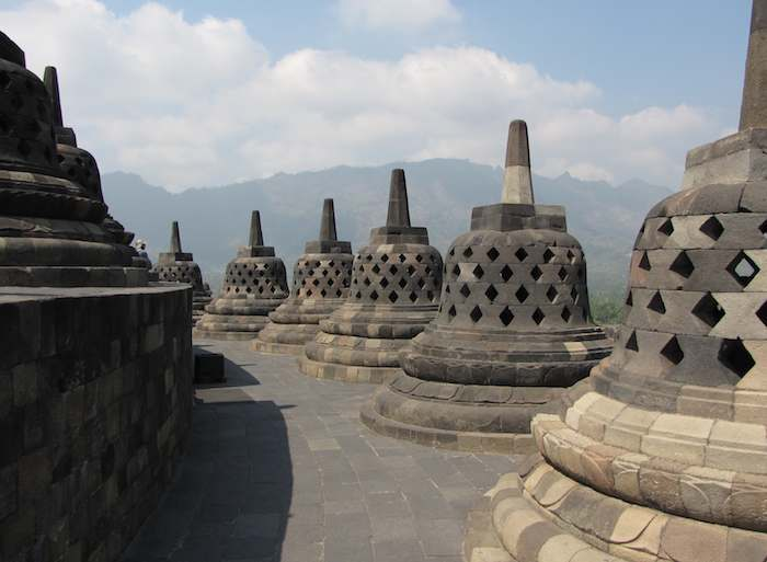 photo of stupas at Borobudur Buddhist temple with mountains in the background