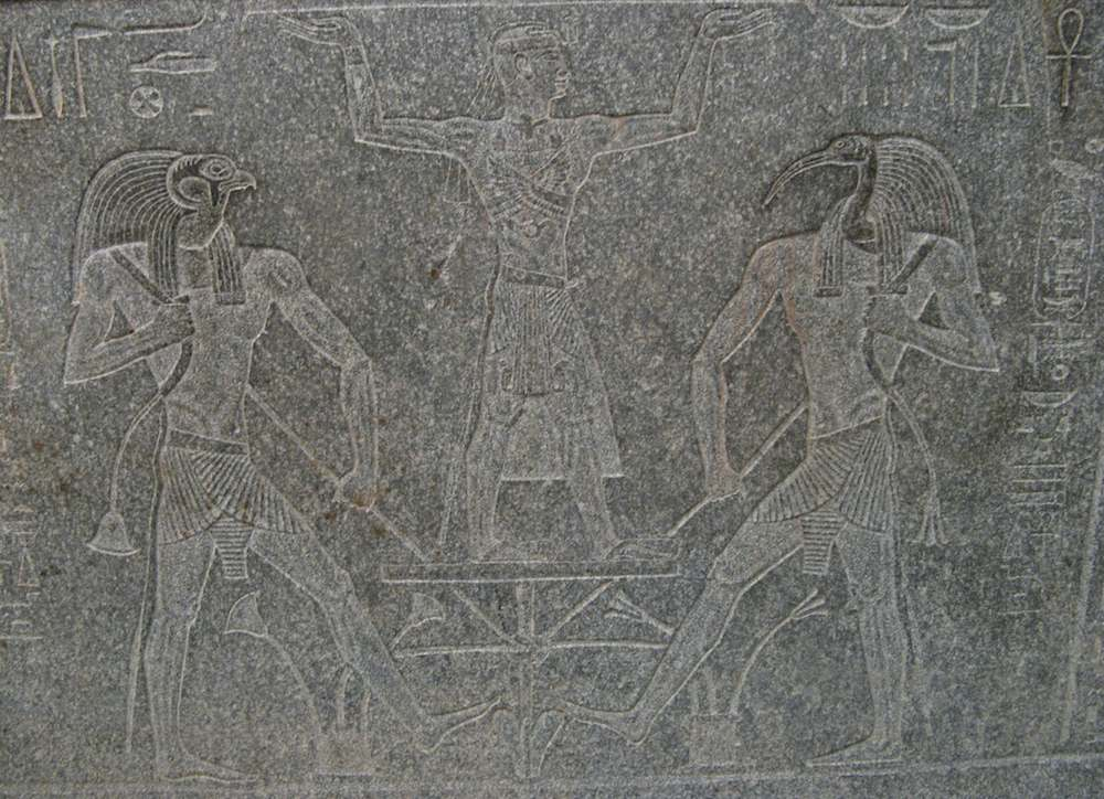 Egyptian carving of figures into a stone sarcophagus