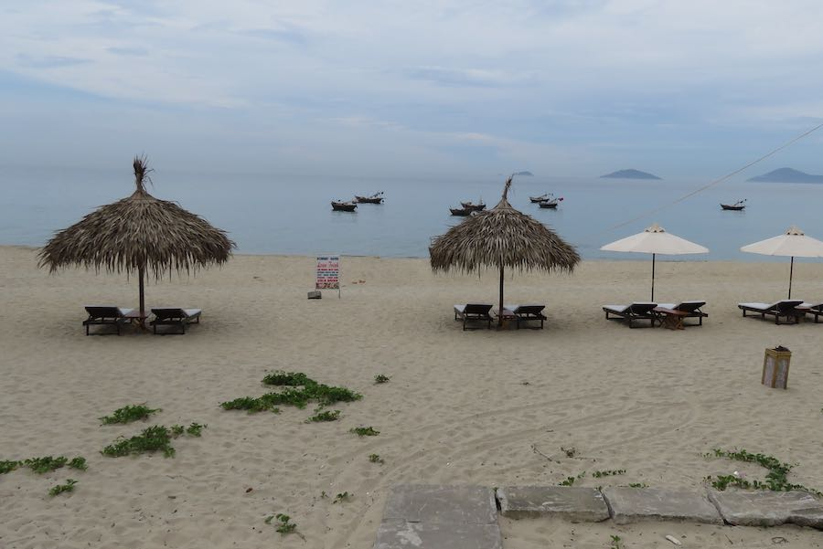 Beach with reclining chairs and thatched toped umbrella looking into the ocean with small boats in the view